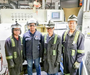 Arrivés en octobre au pays, les Philippins Lloyd Sampang, Julius Asi, Fernando Gervacio et Ulyven Alcantara savent déjà se rendre indispensables dans l'usine de Fonderie Poitras, à L'Islet. On les voit ici devant une noyauteuse de l'entreprise, une machine qu'ils ont eux-mêmes installée et inspectée dans le cadre du premier mandat qui leur a été confié par leurs patrons.