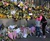 Des enfants observent les fleurs déposées sur le grillage qui entoure le Parlement britannique en hommage aux victimes de l'attaque.