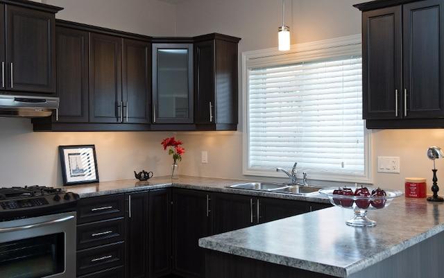 La cuisine est joliment organisée et offre beaucoup d'espaces de rangement, dont un compartiment pour four micro-ondes, et de plans de travail. Les parents apprécieront l'évier double sous la grande fenêtre ouvrant sur la cour.