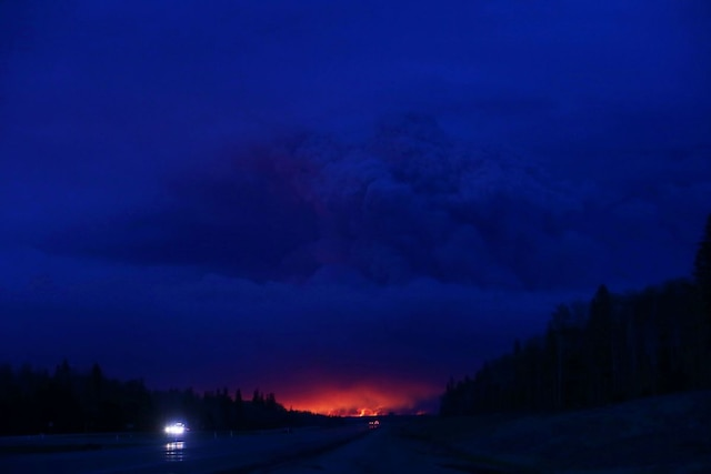 Une photo stupéfiante prise mercredi des flammes au loin dans la pénombre.