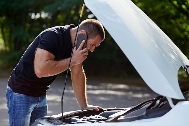 Man calling someone for help with his broken car