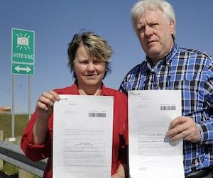Denis Tanguay et sa conjointe Diane Chouinard montrent la contravention qu'ils ont reçue après leur passage devant le radar photo permanent de l'autoroute 20 à Lévis.