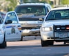 A Codiac RCMP officer takes cover behind a police vehicle in Moncton