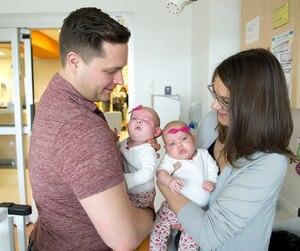 Chloe, dans les bras de son père Craig Hasilo, est née sans voies nasales ni œil gauche. À droite, sa mère Joelle Hasilo et sa jumelle Evelyn.