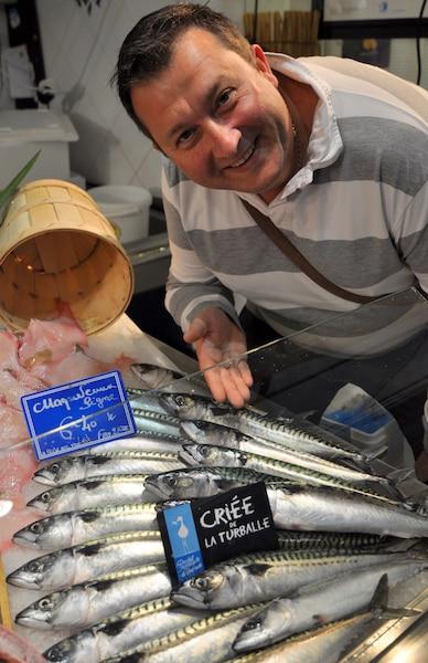 Un chef en extase devant des poissons frais.