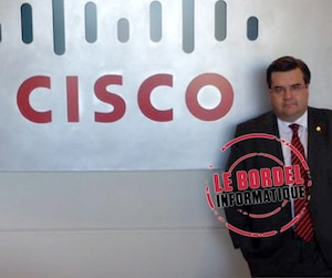 Denis Coderre pose devant le logo de l'entreprise Cisco, qu'il a visitée en octobre 2014.