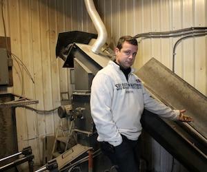 Patrick Desautels montre des copeaux de bois qui lui permettent de chauffer ses serres où poussent ses légumes à la biomasse.