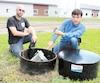 Jonathan Lampron, de la ferme Alampco, et Simon Massé, propriétaire de Puitbec, montrent le puits en angle qui permet de sortir plus d'eau du sol. M.Massé a une boussole dans la main, qu'il utilise lorsqu'il creuse l'installation.