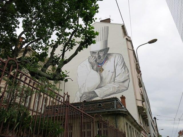 Portrait de Paul Bocuse, pape de la gastronomie française,  devant les Halles de Lyon, nommées en son honneur.
