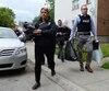 Cinq policiers ont quitté l'appartement du suspect jeudi avec les mains remplies de sacs, de documents, d'un bac et d'au moins un ordinateur.