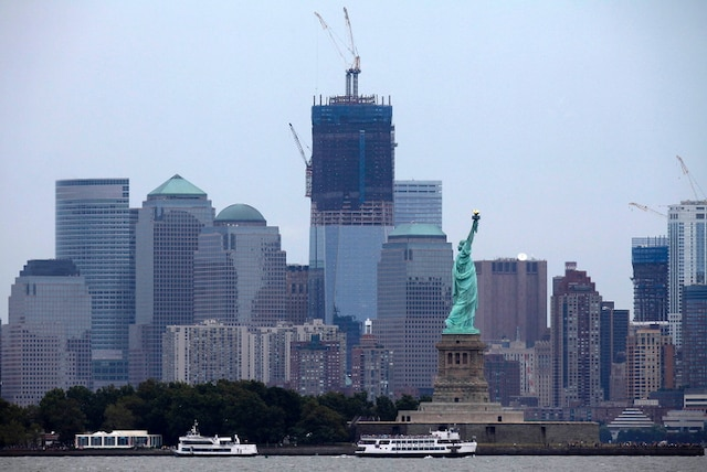 The under-construction One World Trade Center (C) stands tall on New York's Lower Manhattan skyline, behind the Statue of Liberty, as seen from Bayonne, New Jersey, August 6, 2011. New York will mark the 10th anniversary of the attack on the World Trade Center with ceremonies on September 11. REUTERS/Gary Hershorn (UNITED STATES - Tags: CITYSCAPE DISASTER)