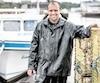 Terry Arsenault pose fièrement devant son bateau dont il est le propriétaire. Chaque année, il pêche les homards pendant dix semaines et met à l'eau jusqu'à 400casiers dans les environs de l'île.