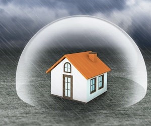 shield covering home under rain, insurance concept