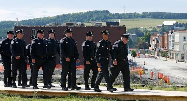 Des pompiers marchent un à la suite de l'autre près le l'église Sainte-Agnès, à Lac-Mégantic, le 6 juillet 2014.