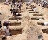 Des hommes creusent des tombes les unes à côté des autres en prévision de l'inhumation des jeunes victimes.