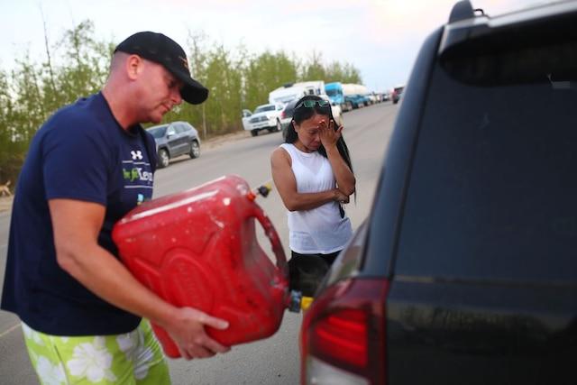 Marilou Wood retient ses larmes pendant que son mari, Jim Wood, remplit leur voiture d'essence à partir d'un réservoir.