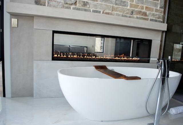 La salle de bains ultramoderne comporte un foyer au gaz permettant de voir la chambre principale.