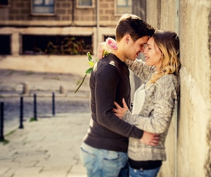 happy couple with rose in love kissing on street for Valentines