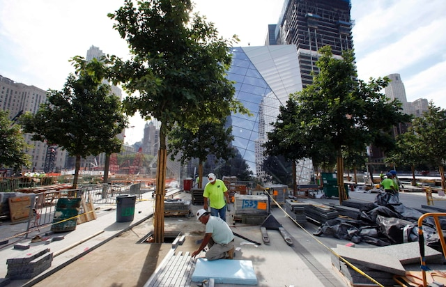 Workers install stone and pavers on the main plaza area as work continues on the National September 11 Memorial and Museum at the World Trade Center site in New York July 28, 2011. The memorial is scheduled to be dedicated on September 11, 2011, the 10th anniversary of the attacks on the World Trade Center. REUTERS/Mike Segar (UNITED STATES - Tags: DISASTER SOCIETY)