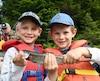Deux jeunes pêcheurs heureux d'avoir capturé cette belle truite arc-en-ciel dans les eaux du lac Resserré.