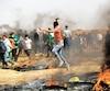 Un manifestant palestinien lançait des pierres vendredi, lors d'affrontements avec l'armée israélienne près de la frontière avec l'État hébreu.