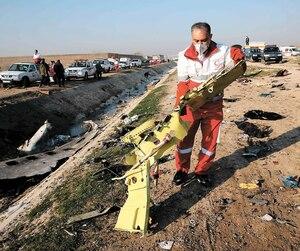 Un secouriste ramasse des débris de l'avion qui a été abattu mardi soir.