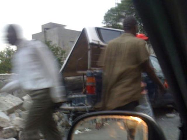 Cette photo obtenue de Twitter nous montre des Haïtiens qui sont descendus sur une rue lourdement endommagée.