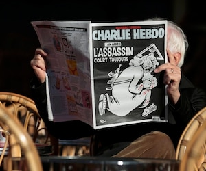 "A man reads the latest edition of French weekly newspaper Charlie Hebdo with the title ""One year on, The assassin still on the run"" on a cafe terrasse in Nice"