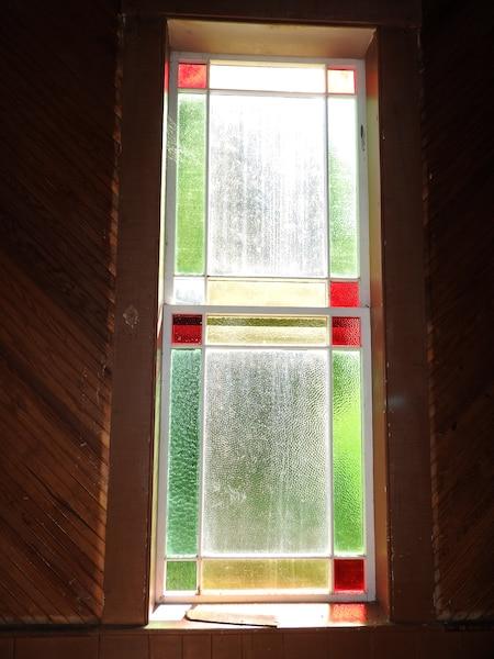 L'église dispose de huit vitraux comme celui-ci. Ils sont montés sur des châssis de bois à guillotine et chaque carreau de verre ambré est retenu par des baguettes de bois.