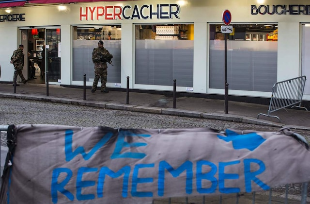French soldiers patrol outside the Hyper Cacher, a kosher supermarket, near Paris, on January 5, 2016, after France's President attended a commemorative ceremony to pay tribute to the victims of the terrorist attack on the supermarket on January 9, 2015. French President Francois Hollande today kicked off a week of commemorations marking the jihadist rampage in Paris that began with an assault on satirical weekly Charlie Hebdo and lasted three days, claiming 17 lives. The president and mayor unveiled a plaque at the Hyper Cacher, in an eastern suburb where four Jews -- three shoppers and an employee -- were killed during a horrifying hostage drama. / AFP / POOL / IAN LANGSDON