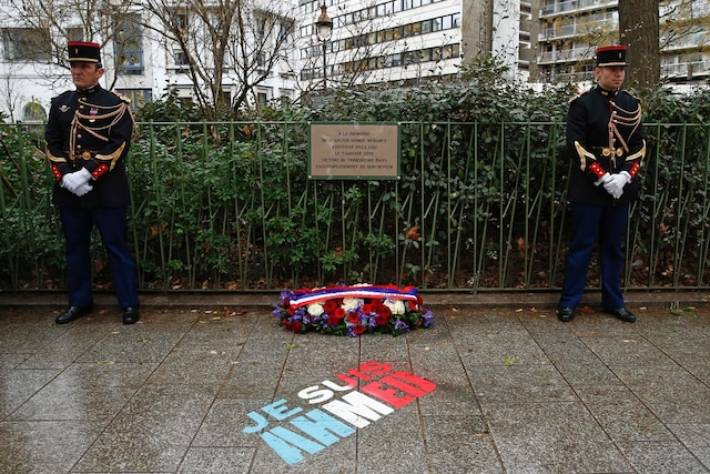 TOPSHOT - French gendarmes stand near a commemorative plaque on January 5, 2016 during a ceremony at the site where policeman Ahmed Merabet was killed during the last year's January attack in Paris.   A total of 17 people were killed in the three days of attacks dubbed