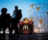 Même si McDonald's a mis fin à son entente avec le CIO, le géant américain de la restauration rapide reste associé aux Jeux à l'échelle locale. Sur la photo, des passants sont photographiés près d'un restaurant McDonald's dans la zone olympique de Gangneung.