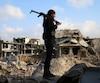 Un combattant rebelle se tient au milieu des immeubles en ruines à Daraa.