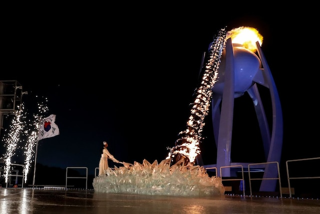 South Korean figure skater Kim Yu-na lights the cauldron with the Olympic Flame during the opening ceremony of the Pyeongchang 2018 Winter Olympic Games at the Pyeongchang Stadium on February 9, 2018. / AFP PHOTO / POOL / David J.PHILIP