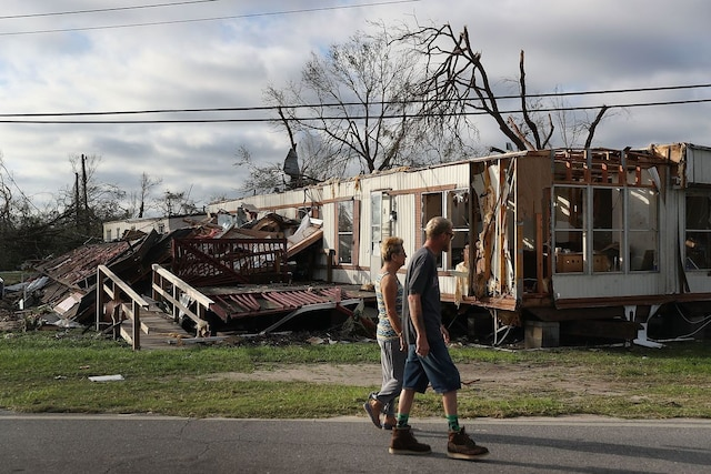 PANAMA CITY, FL - OCTOBER 11: People walk past a home destroyed by Hurricane Michael on October 11, 2018 in Panama City, Florida. The hurricane hit the Florida Panhandle as a category 4 storm.   Joe Raedle/Getty Images/AFP == FOR NEWSPAPERS, INTERNET, TELCOS & TELEVISION USE ONLY ==
