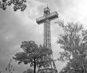 La croix est plus belle de loin que de près. Elle n'est en réalité qu'un paquet de tiges de métal mises ensemble. Mais son but est d'être vue à distance. Surtout la nuit. Ce symbole illustre bien Montréal sur les cartes postales.