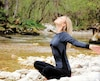 Happy smiling young woman breathing fresh air, relaxing in nature, doing stretching exercises. Freedom concept