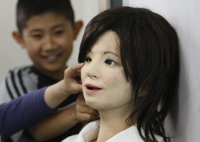 A humanoid robot named 'Saya' is touched by school pupils as she takes on a role as a school teacher at an elementary school in Tokyo