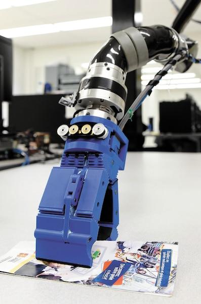 Une autre main robotisée (à droite) permet de saisir avec délicatesse des petits objets comme une feuille de papier.