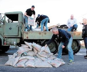 À l'aide d'un vieux camion de l'armée, Pat Chartrand (à gauche) aide des sinistrés des crues printanières à Gatineau à transporter des sacs de sable.