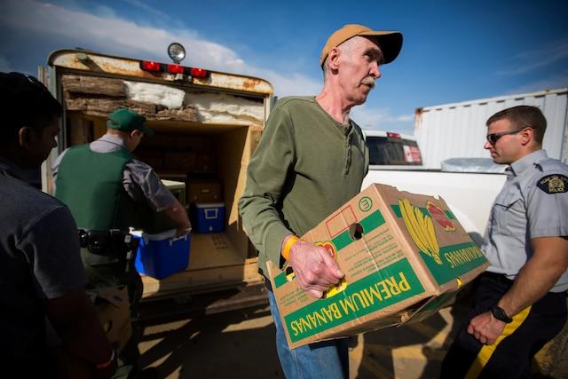 Des bénévoles transportent de la nourriture à l'intérieur du centre communautaire d'Anzac.