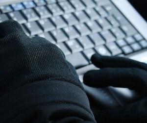 Cyberattaque mains gantées ordinateur pirate piratage