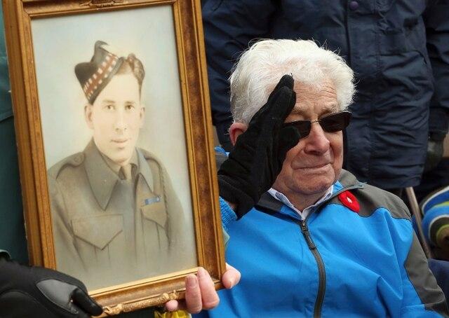 Un vétéran de la Seconde Guerre mondiale se tient à côté de son portrait datant de cette époque, à Ottawa.