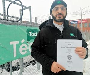 Le chauffeur Mohammed Laouni montre le projet de convention collective mort dans l'œuf, quelques heures après l'annonce de la fermeture de Téo Taxi devant la centrale de la rue Saint-Patrick, à Montréal. Il est fâché de voir l'aventure se terminer ainsi.
