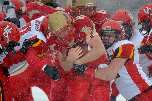 Sébastien Lévesque du Rouge et Or de l'Université Laval se fait plaquer par la défensive des Dino's de l'Université de Calgary  pendant le match de la Coupe Vanier.