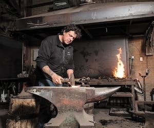 Luc Lapointe, qui travaille dans son atelier de Forges Urbaines, une entreprise située en plein cœur de l'arrondissement de Saint-Léonard à Montréal, attend depuis un an un Français afin qu'il puisse lui donner un coup de main.