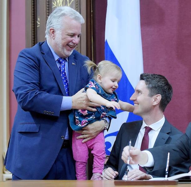 Philippe Couillard accompagné du nouveau ministre des Transports, André Fortin, et de sa petite fille Élodie.