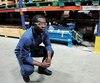 Thomas Mbock pose dans l'entrepôt chez Technosub, devant le technojet, la pompe qu'il tente d'améliorer.