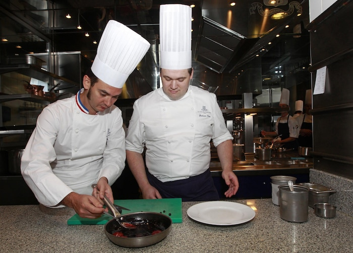 French head chef Delarbre and head pastrycook Caron prepare a honey desert in the kitchen of the Tour d'Argent restaurant in Paris