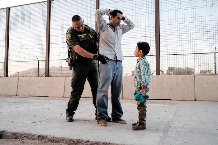 Le 16 mai, José, ici avec son fils José Daniel, est fouillé par l'agent des douanes américaines Frank Pino à El Paso, au Texas, après avoir passé un mois à traverser le Mexique depuis le Guatemala.
